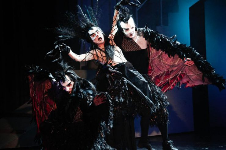 Przechyloną w tył Wroniastą podtrzymuje jedna z Wron, druga siedzi przykucnięta z lewej strony. Czerwono-czarne kostiumy z czarnymi piórami, białe, groźnie wyglądające maski.
