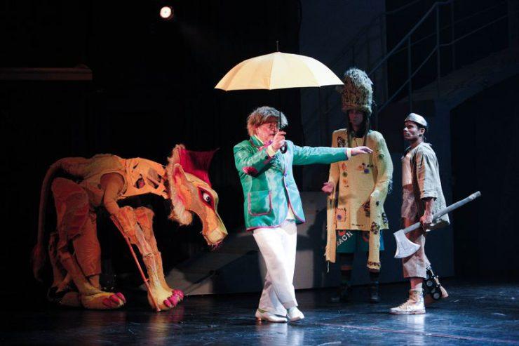 Oz w zielonej marynarce, z rozłożonym żółtym parasolem. Obok niego, z lewej strony znajduje się Lew, po prawej – Strach na Wróble i Blaszany Drwal.