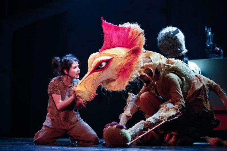 Dorotka przysiadła na kolanach obok Tchórzliwego Lwa, zwrócona w jego stronę, trzyma w dłoniach pysk zwierzęcia, coś do niego mówi.