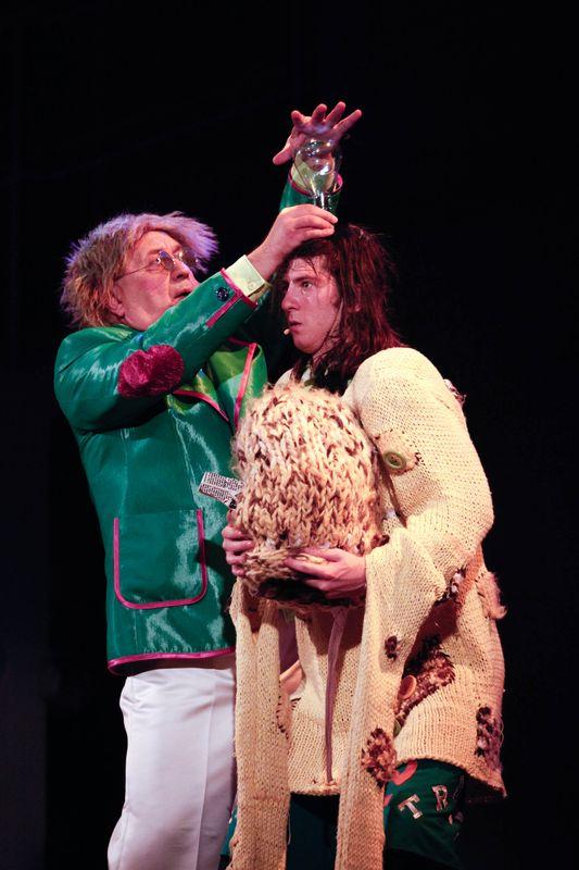 Rozczochrany Oz unosi dłonie nad głową Stracha na Wróble, trzymającego w rękach olbrzymią czapkę.