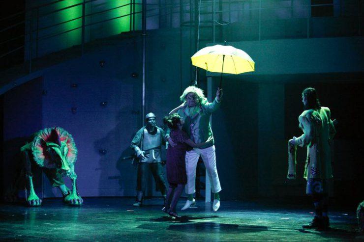 Na środku rozczochrany Oz, w lewej dłoni ma otwarty parasol, zaczyna unosić się w górę. Przytrzymuje go Dorotka, przyglądają się: Lew, Blaszany Drwal i Strach na Wróble.