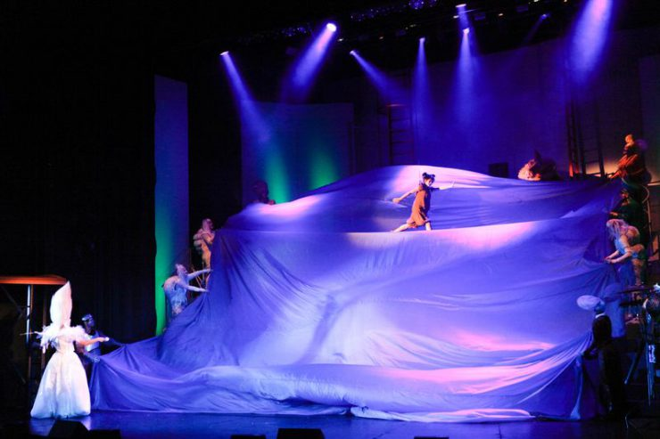 Scena spowita dużą, oświetloną fioletowo, falującą tkaniną. U góry unosi się Dorotka, po obu stronach stoją bohaterowie spektaklu.