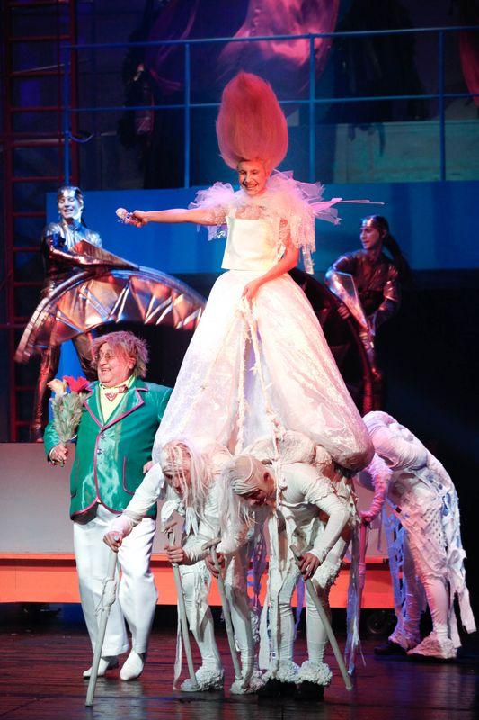 Szeleszcząca w białej, długiej sukni, unoszona na plecach Manczkinów, postaci w białych kostiumach, obok niej, z lewej strony Oz, w tle widoczne Kalidachy.