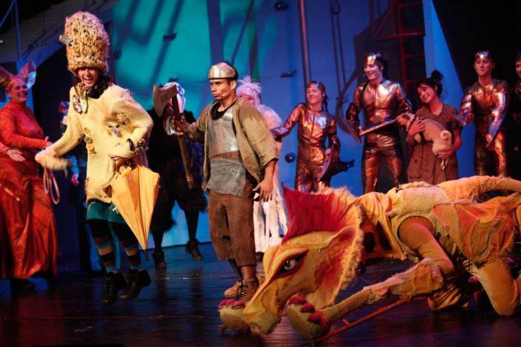 Na pierwszym planie, od lewej: Strach na Wróble, Blaszany Drwal i Lew. W tle śpiewający, inni bohaterowie spektaklu.