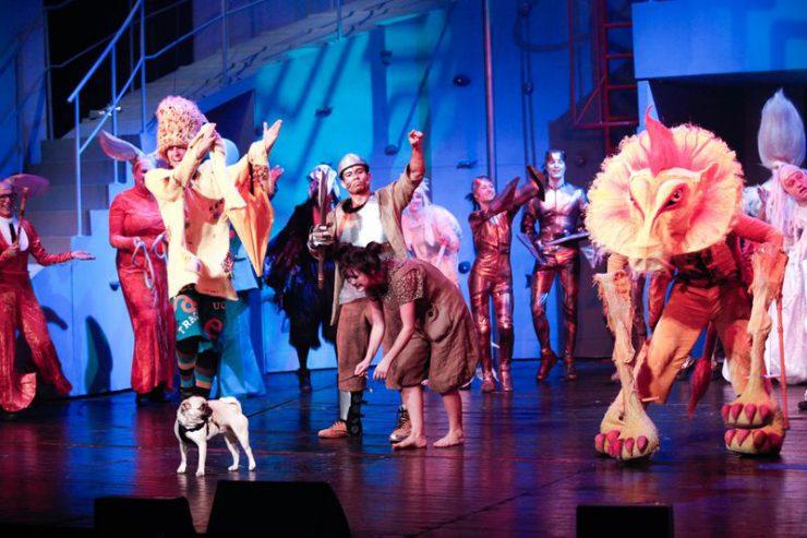Obsada spektaklu kłania się publiczności. Na pierwszym planie Strach na Wróble, Blaszany Drwal, Dorotka z psem i Lew.