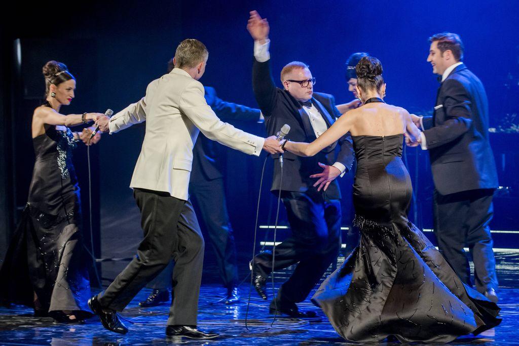 Trzy kobiety i trzech mężczyzn trzyma się za dłonie, tworząc taneczne kółko. Artystki mają na sobie czarne, wieczorowe suknie, mężczyźni ubrani są w eleganckie smokingi, dwaj – w czarne, jeden – w biało-czarny. Tańczą wokół konferansjera, który z poważną miną przybiera taneczną pozę, z prawą ręką uniesioną do góry.