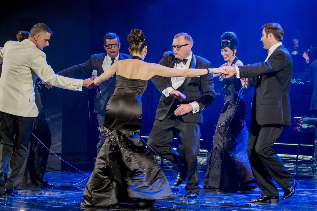 Trzy kobiety i trzech mężczyzn trzyma się za dłonie, tworząc taneczne kółko. Artystki mają na sobie czarne, wieczorowe suknie, mężczyźni ubrani są w eleganckie smokingi, dwaj – w czarne, jeden – w biało-czarny. Tańczą wokół konferansjera, jasnowłosego mężczyzny w okularach, który z poważną miną przybiera taneczną pozę.