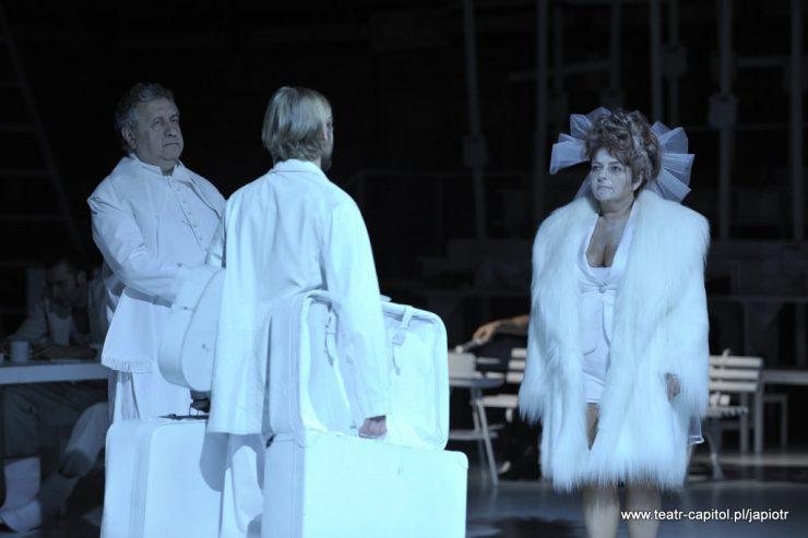 Z lewej strony stoi starszy mężczyzna w stroju duchownego, tyłem stoi mężczyzna w białym stroju, trzymający walizki, zwrócony twarzą w stronę kobiety ubranej w białe futro, z woalem upiętym we włosach.