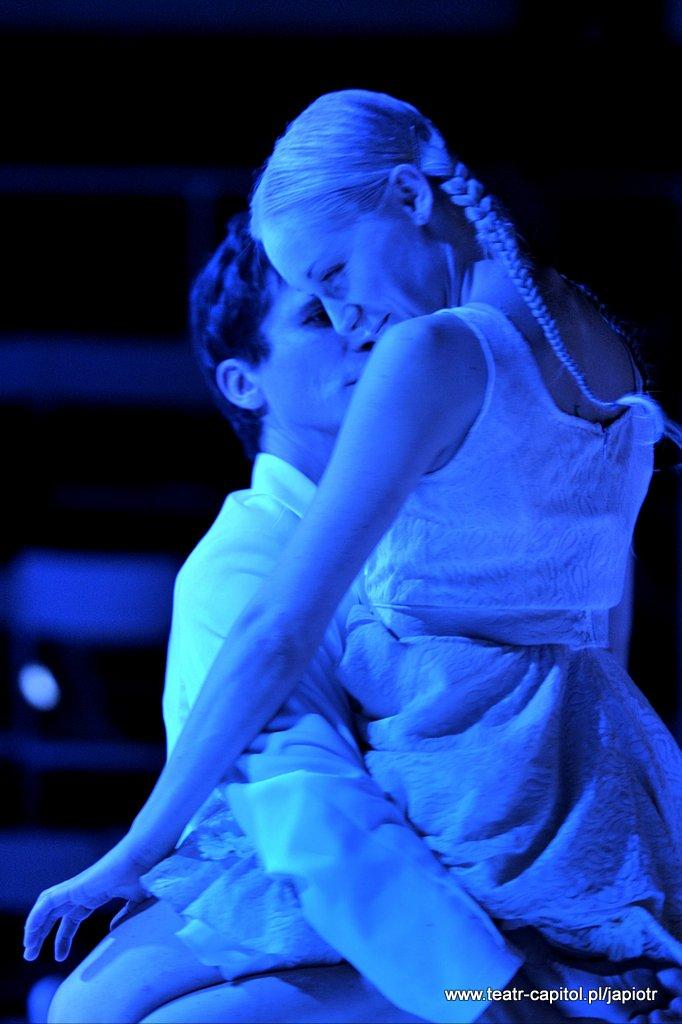 Na kolanach Piotra Rivière`a siedzi młoda kobieta z blond warkoczykami, zwrócona przodem do niego.