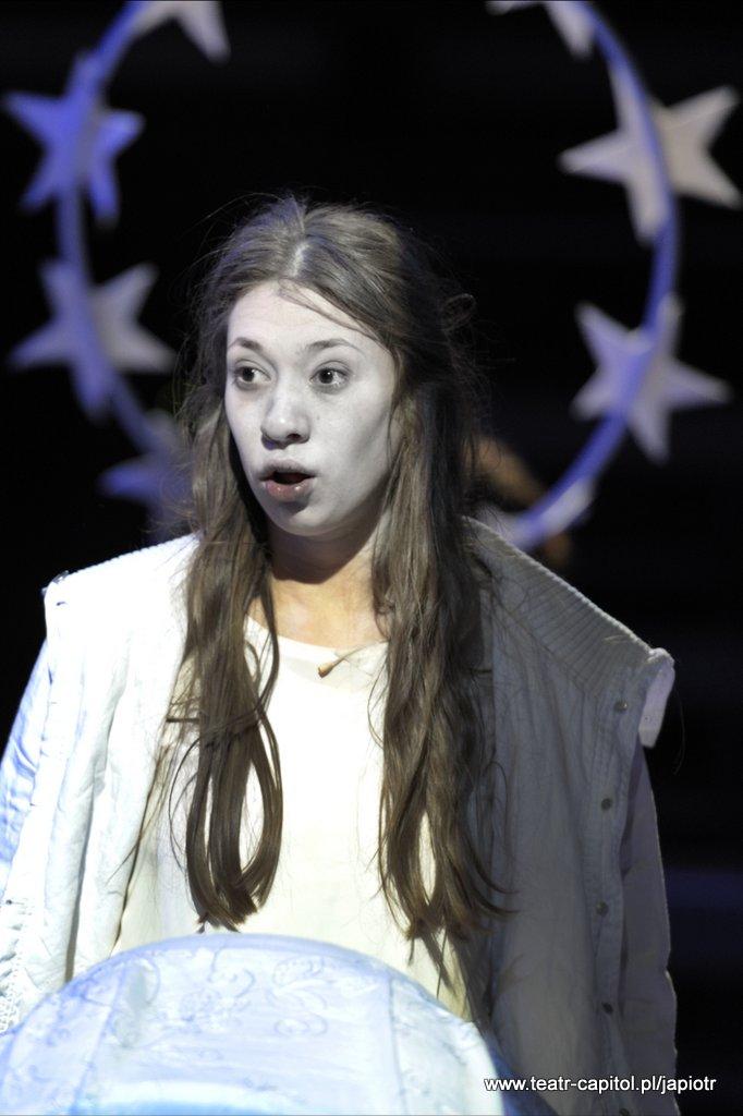 Długowłosa Victoria w białym stroju, z aureolą Amien okalającą jej głowę.
