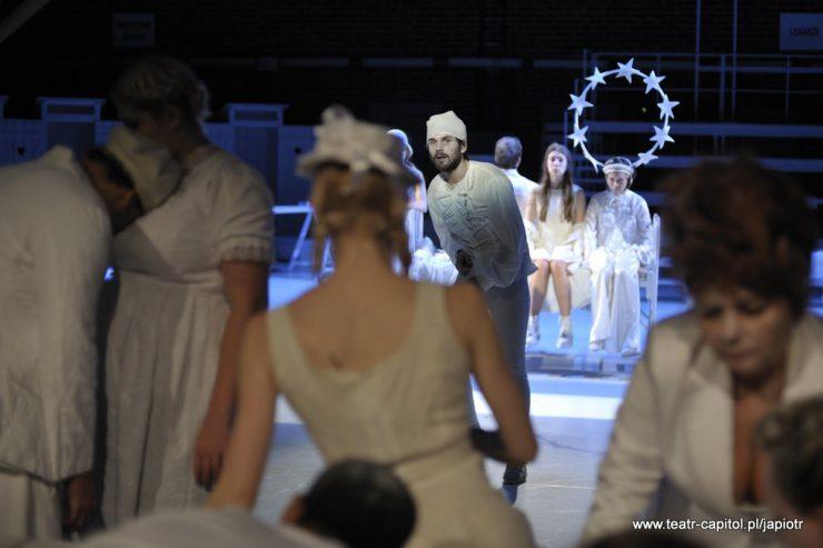 Na pierwszym planie grupka osób tyłem, w centrum kadru stoi Prosper, za nim, w tle, widoczne ubrane na biało Victoria i Amien.