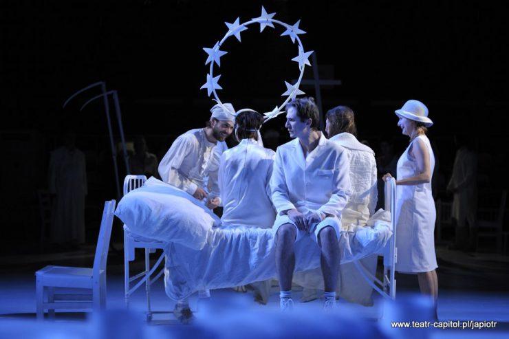 Cztery osoby siedzą na szpitalnym, białym, metalowym łóżku, dwie widoczne z tyłu. Z przodu siedzi Piotr Rivière, bokiem, przy oparciu łóżka stoi uśmiechnięta Rivièrowa.