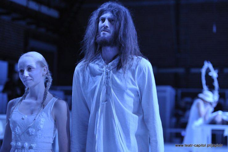Wysoki, zarośnięty, długowłosy mężczyzna w białej koszuli stoi obok młodej dziewczyny z blond warkoczykami, w lekkiej, białej sukience.