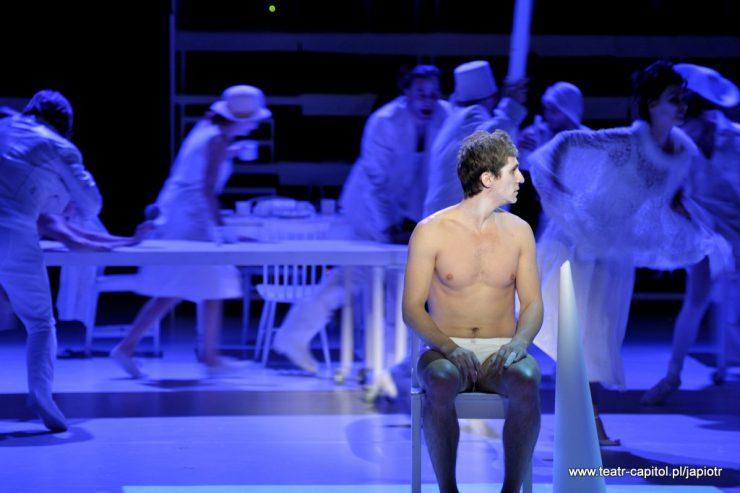 Na pierwszym planie siedzi Piotr Rivière, oświetlony jasnym światłem, z gołym torsem i białą twarzą, z głową zwróconą profilem w prawą stronę. Za nim korowód postaci w ruchu, w niebieskiej poświacie.