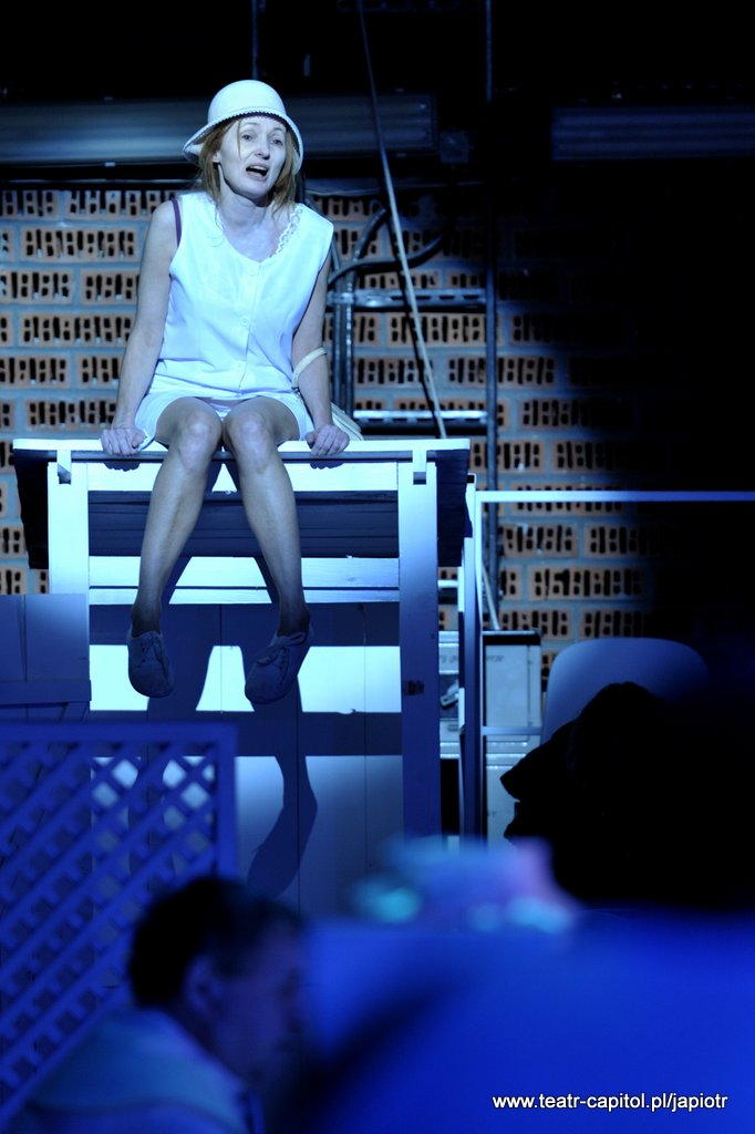 Na białej, wysokiej konstrukcji wyglądającej jak otwarta szafa, siedzi Rivièrowa. Oświetlona, w kapeluszu i ubrana na biało, ma otwarte usta.
