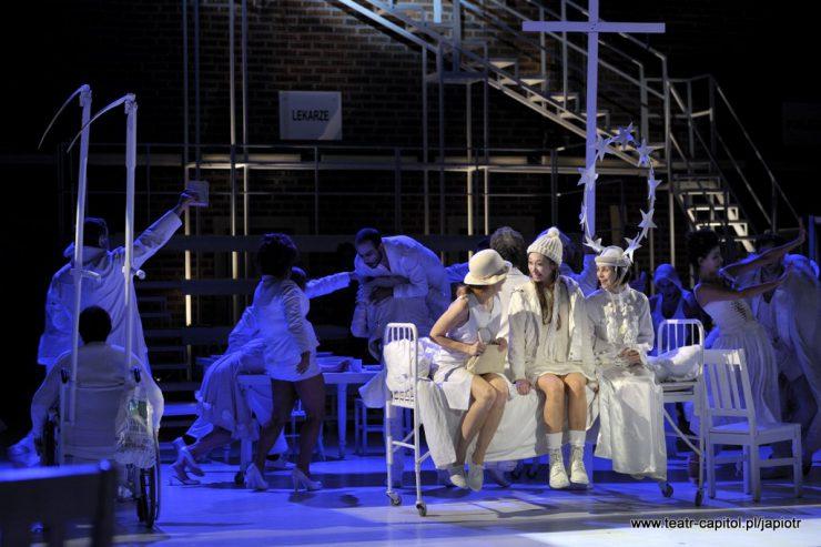 """Na pierwszym planie oświetlone jasno trzy kobiety, siedzące na metalowym, szpitalnym, białym łóżku. Z lewej siedzi Rivièrowa, skierowana ku patrzącym na nią Victorii i Amien. Za nimi widać inne postaci, wysoki krzyż i tablicę z napisem """"Lekarze""""."""