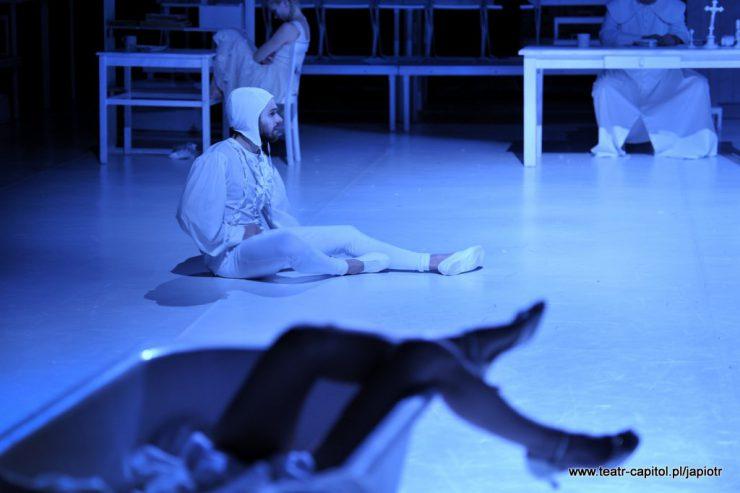 Na białej podłodze siedzi bokiem Prosper, mężczyzna ubrany w białe, obcisłe spodnie, koszulę z żabotem, z nakryciem głowy przypominającym czepek. Na pierwszym planie widoczne kobiece nogi wystające z wanny.