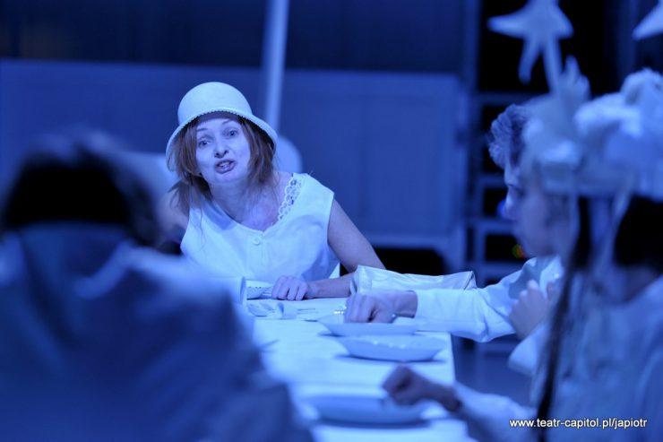Przy stole siedzi kilka osób, jedna tyłem, zwrócona w stronę Rivièrowej, znajdującej się w centrum kadru. Kobieta coś mówi, patrząc w kierunku postaci widocznej z tyłu.