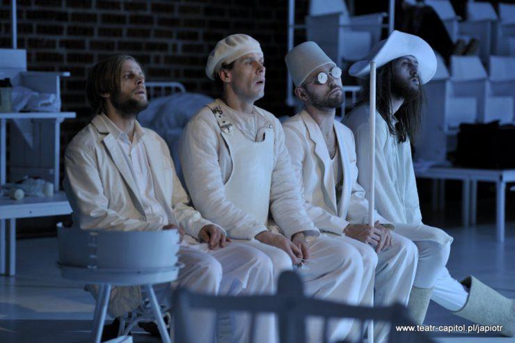 W rzędzie, obok siebie, siedzi czterech mężczyzn. Ubrani na biało, trzej z nakryciami głowy. Patrzą w tym samym kierunku, poza ślepcem, który ma oczy ukryte za okularami i trzyma w dłoniach białą laskę.