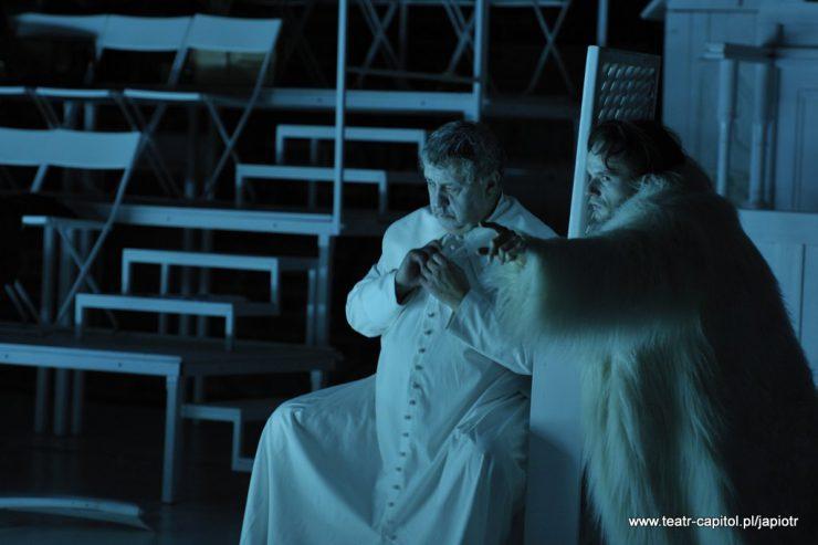 Starszy mężczyzna w szacie duchownego siedzi przy konfesjonale, po drugiej stronie konfesjonału znajduje się mężczyzna w białym, futrzanym okryciu, lewą ręką z wyciągniętym palcem coś wskazuje, patrząc w tym kierunku.