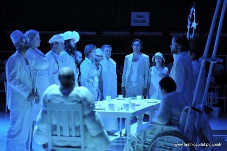 """Wokół zastawionego naczyniami stołu stoi kilkanaście osób w bieli, dwie siedzą. Niebieskawe światło, z tyłu widoczna tablica z napisem """"Opinia publiczna""""."""