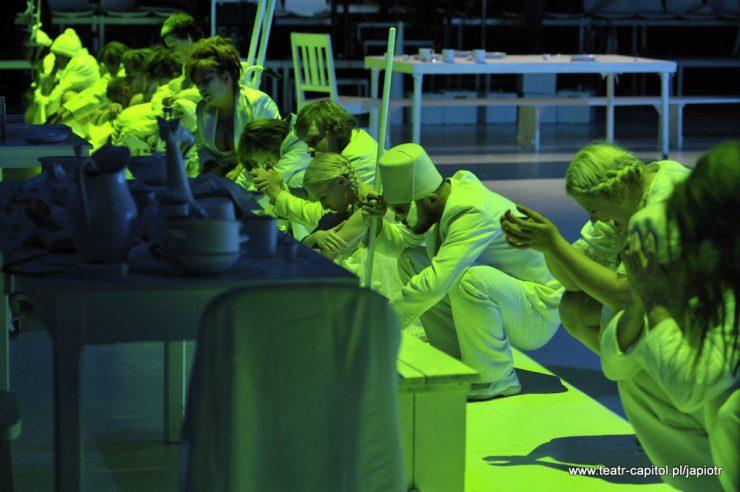Z lewej strony widoczny zastawiony naczyniami stół, za nim przykucnięte, ustawione w rzędzie osoby, oświetlone seledynowym światłem.