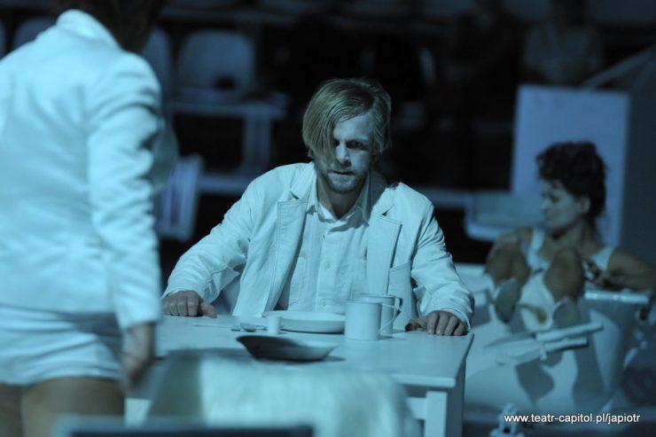 Na środku kadru mężczyzna w białej marynarce i koszuli siedzący za stołem zastawionym naczyniami. Rozłożone ręce opiera o blat stołu, nie patrzy w kierunku odwróconej tyłem osoby, która stoi przed nim, z lewej strony.