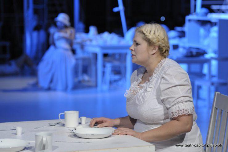 Po prawej stronie, przy stole zastawionym naczyniami, siedzi kobieta w bieli, odwrócona bokiem, profilem skierowana ku lewej stronie, dłonie opiera o blat stołu.