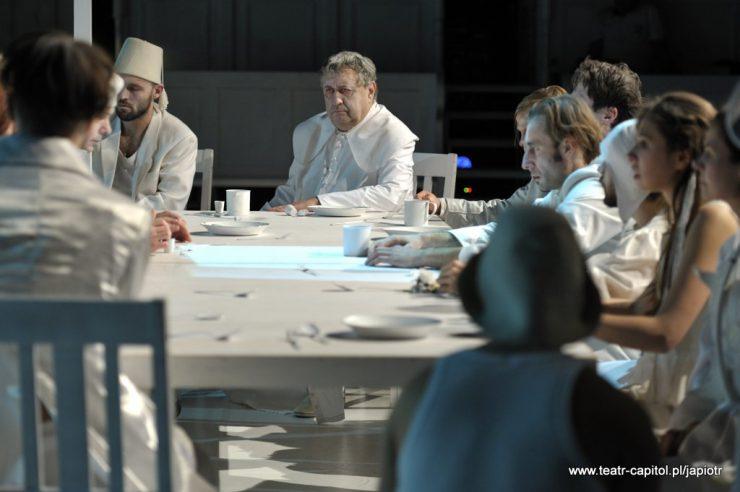 Duży, biały, zastawiony naczyniami stół, wokół niego siedzą kobiety i mężczyźni ubrani na biało. W głębi widoczny starszy mężczyzna w stroju duchownego.