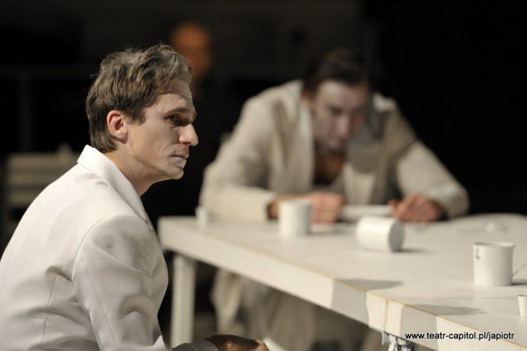 Z lewej strony siedzi Piotr Rivière, twarz ma zwróconą profilem w prawą stronę. W tle widać siedzącego przy stole ojca Rivière.