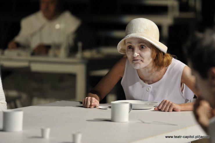 Rivièrowa siedzi za stołem, przed nią leży talerz, stoi kubek. Kobieta w dłoni ściska łyżkę, na pomalowanej na biało twarzy ma nieładny grymas, lekko wytrzeszcza oczy, zwraca się w kierunku osób, które siedzą z nią przy stole.