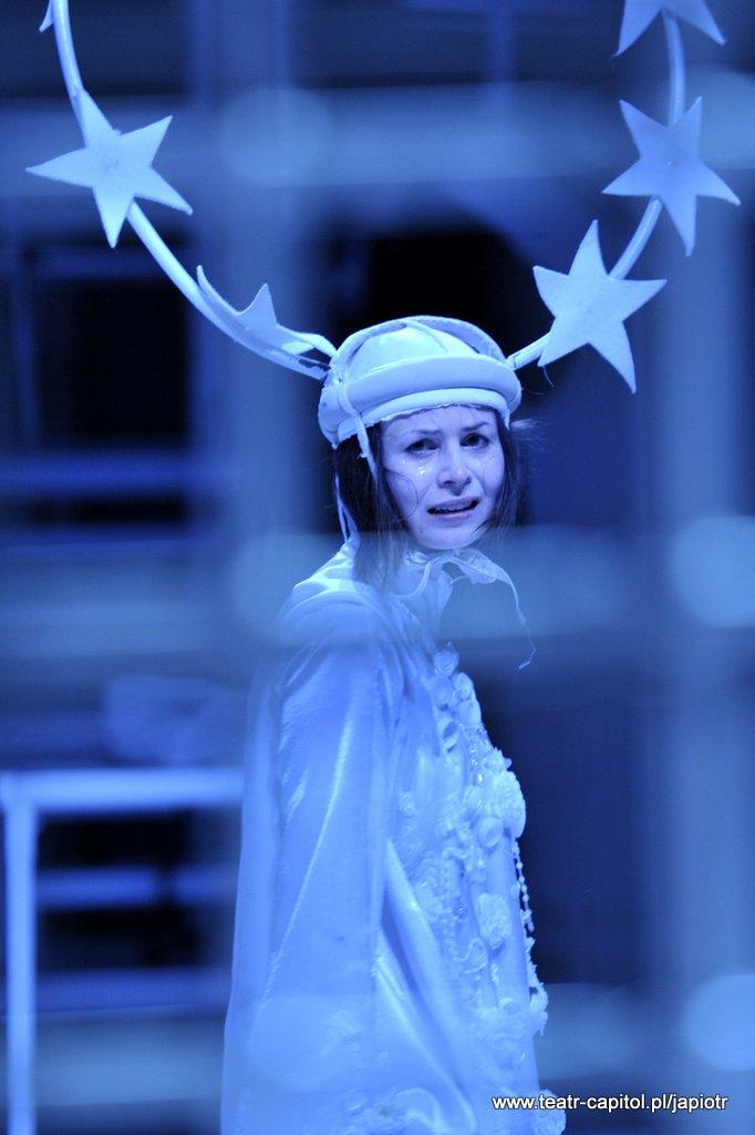 Smutna, płacząca kobieta w białym stroju, z nakryciem głowy, do którego jest przyczepiona duża aureola z gwiazdami.
