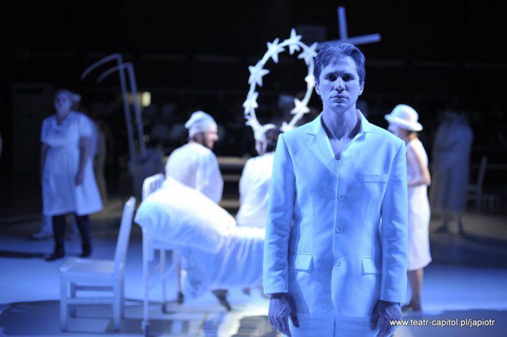 Na pierwszym planie stoi, zwrócony twarzą do widza, Piotr Rivière, w białej marynarce i spodniach, patrzy przed siebie. W tle inne postaci.