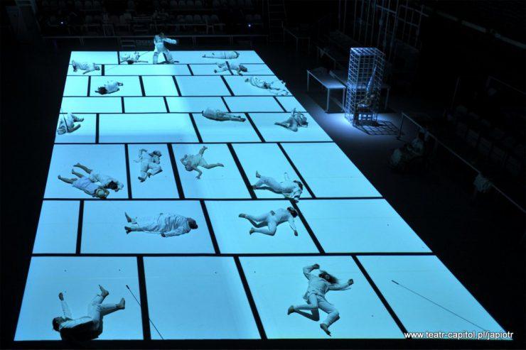 Biała, podzielona na osobne części, płaszczyzna podłogi. W różnych jej miejscach, oddzielonych liniami, leżą postaci – bohaterowie spektaklu, w pozach bezwładnych, nieskoordynowanych.