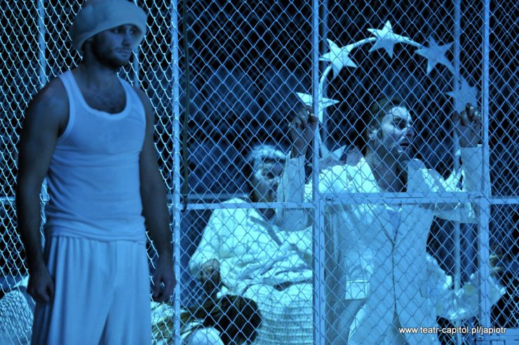 Z lewej strony stoi młody mężczyzna w białym podkoszulku, spodniach i dziwnym nakryciu głowy. W tle klatka z siatki, wewnątrz znajduje się Rivière – ojciec, przytrzymuje uniesionymi dłońmi siatkę, za nim widoczne inne osoby.