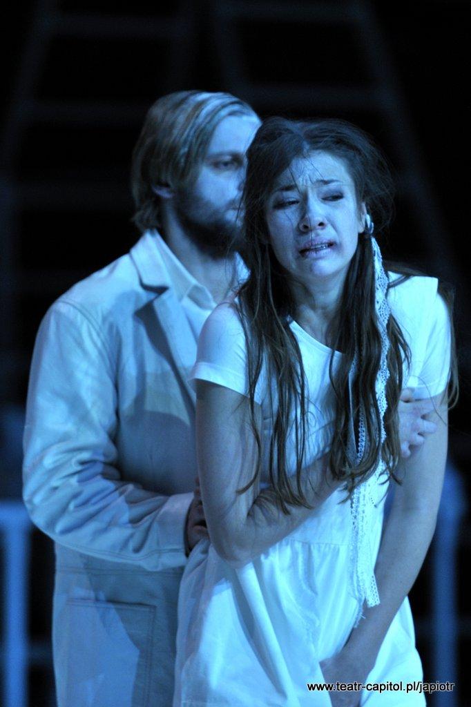 Płacząca młoda kobieta z długimi włosami, wyraz rozpaczy na twarzy. Z tyłu stoi, przytrzymując ją w pasie, ubrany na biało, młody mężczyzna.