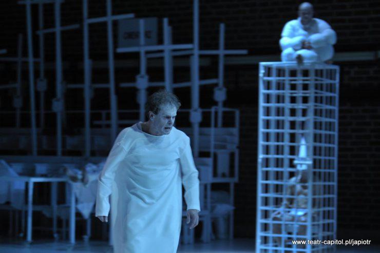 """Na pierwszym planie Młynarz, mężczyzna w białej szacie przypominającej strój szpitalny. Z prawej strony, w tle – konstrukcja klatki, wewnątrz niej ktoś jest. Na górze klatki siedzi człowiek w białym, """"napompowanym"""" kombinezonie. Za Młynarzem wiele wysokich krzyży."""