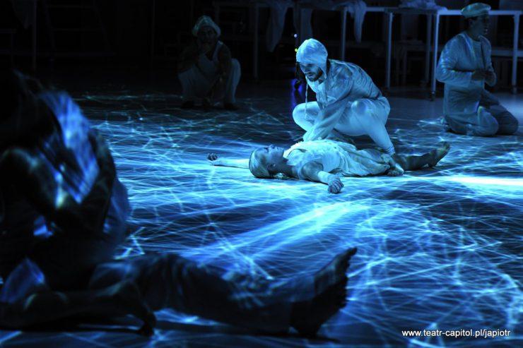 Na podłodze oświetlonej niebiesko, wśród promieni światła leży młoda kobieta. Ma rozłożone na boki ręce, patrzy martwym wzrokiem w górę. Nad nią przykucnięty Prosper, patrzy na kobietę, dotyka jej lewą ręką.