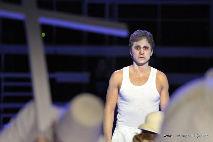 Młody mężczyzna, Piotr Rivière, ubrany w biały podkoszulek i spodnie, z pobieloną twarzą. Patrzy przed siebie, ma smutny wyraz twarzy.