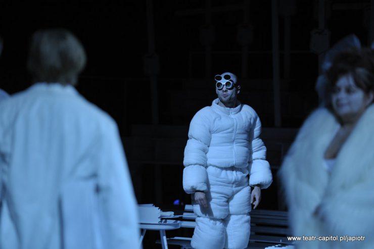 """Pomiędzy dwiema, słabo widocznymi postaciami stoi człowiek w białym stroju, wyglądającym jak puchowy, """"napompowany"""" kombinezon. Mężczyzna, Wędrowiec ma podwójne okulary, nad jednymi szkłami umieszczone są drugie."""