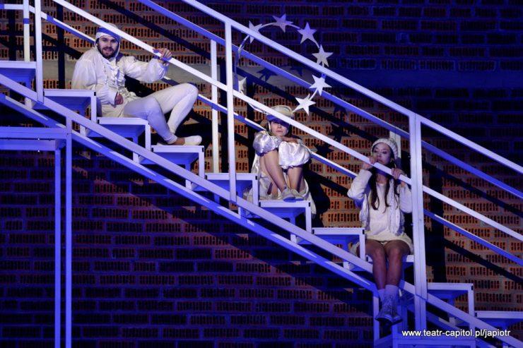 Fragment schodów z wysokimi poręczami. Na ich stopniach siedzą: najniżej kobieta w czapce, na środku Amien w gwiezdnej aureoli, najwyżej – Prosper, mężczyzna w koszuli z żabotem i nakryciu głowy przypominającym czepek.