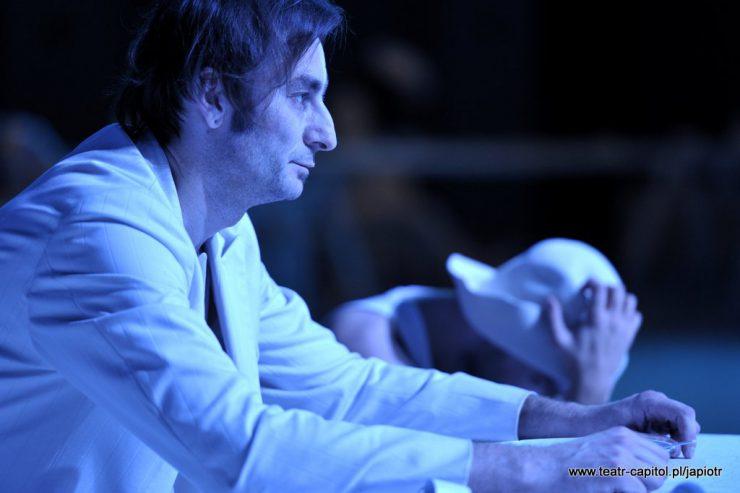 Na pierwszym planie, z lewej strony, mężczyzna w bieli. Ręce trzyma na blacie, patrzy przed siebie. W tle obok niego pochylona w przód postać w kapeluszu.