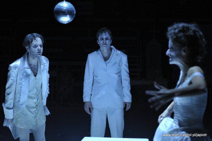 Troje ludzi: z prawej gestykulująca kobieta, z lewej i na środku stoją mężczyźni, patrzą na kobietę. Pomiędzy nimi, u góry, błyszcząca, duża kula.