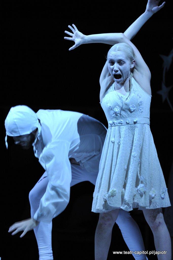 Z lewej strony pochylony mężczyzna w bieli, z nakryciem głowy przypominającym czepek. Obok niego młoda kobieta, z rękami uniesionymi w górę skrzyżowanymi nad głową. Usta otwarte w krzyku, wyraz cierpienia na twarzy.