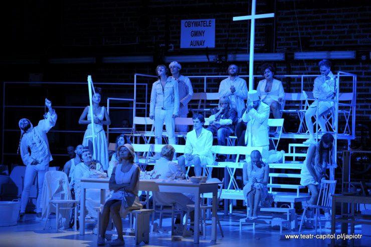 """Trybuna składająca się z kilku poziomów, siedzi na niej kilkanaście osób ubranych na biało, oświetlonych niebieskim światłem. U góry zamontowany duży biały krzyż, obok niego tablica z napisem """"Obywatele Gminy Aunay""""."""