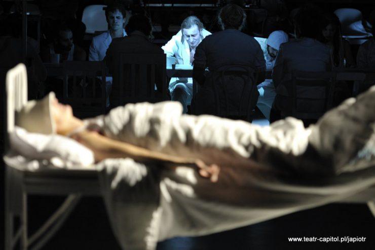 Na pierwszym planie postać w bieli, leżąca w łóżku, w tle widać osoby siedzące przy stole.