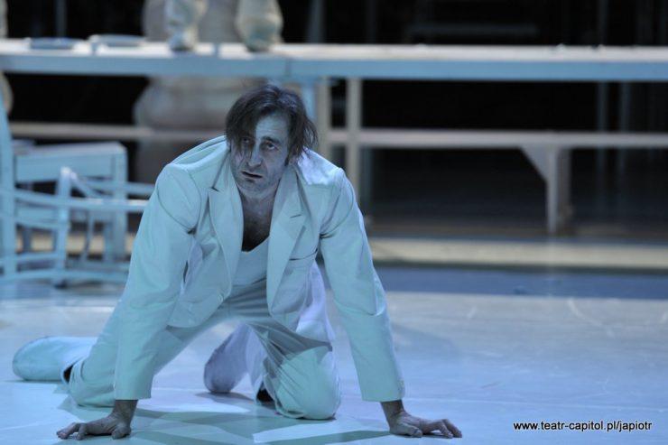Z lewej strony mężczyzna w białej marynarce, spodniach i koszulce. Rivière – ojciec klęczy, opiera się dłońmi o podłogę, patrzy w górę.
