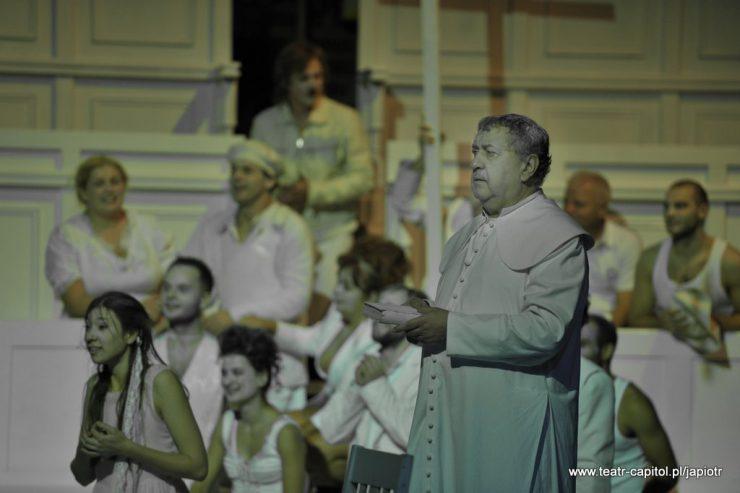 Na pierwszym planie, z prawej strony, stoi starszy mężczyzna w białej szacie duchownego. W tle widać wiele postaci bohaterów spektaklu.