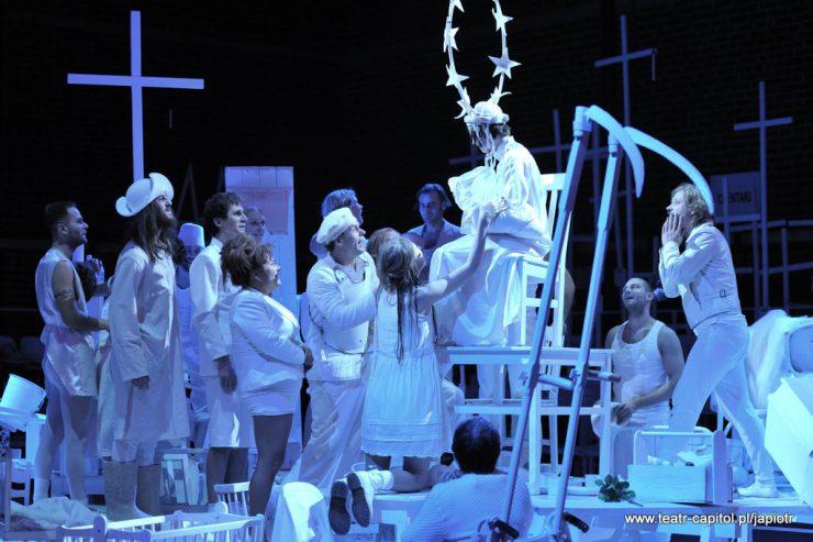 Duża grupa ubranych na biało postaci stoi w kolejce przed tronem, patrzy na siedzącą na nim kobietę z gwiezdną aureolą wokół głowy. Z lewej strony w tle krzyż, z prawej strony - ustawione ostrzem do góry dwie kosy.