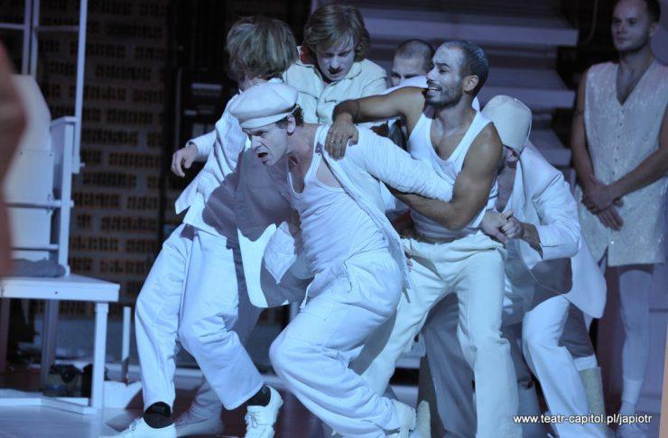 Grupa ubranych na biało mężczyzn. Jeden z nich przytrzymuje Młynarza.